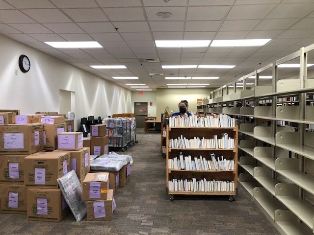 Library staff move books off shelves next to boxes